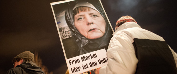 dpatopbilder Ein Teilnehmer einer Kundgebung der Anti-Islam-Bewegung Pegida hält am 12.01.2015 vor einer Kundgebung in Dresden (Sachsen) ein Schild mit der Abbildung von Bundeskanzlerin Merkel mit Kopftuch und der Aufschrift